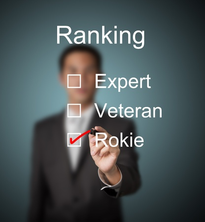 businessman make red mark on rookie ranking photo