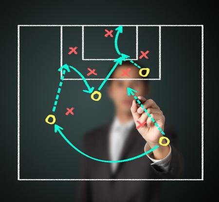 attacking: entrenador de f�tbol por escrito la estrategia de atacar a juego Foto de archivo