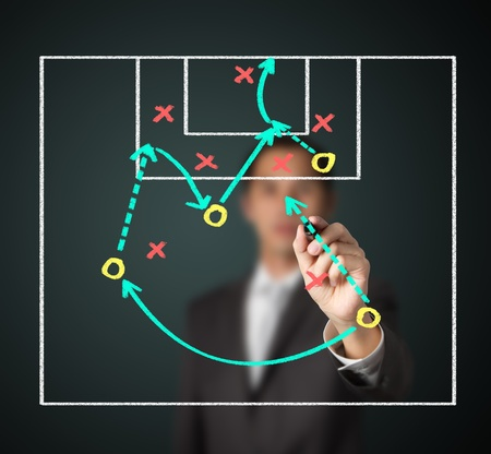 soccer coach writing strategy of attacking game photo
