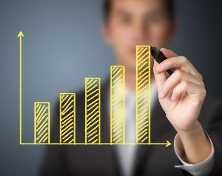 financial performance: businessman drawing upward trend bar chart