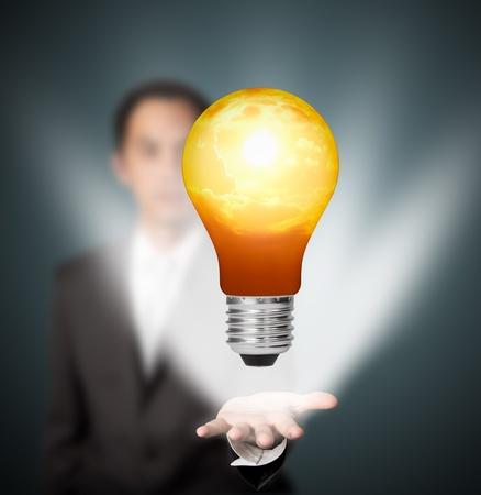 future eco green energy concept - light bulb of solar energy in man hand photo