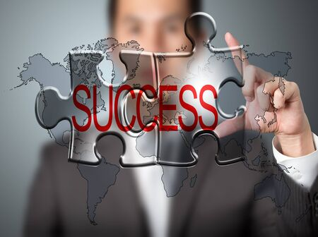 business man holding success connected jigsaw puzzle with world map background photo