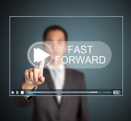 fast forward: uomo d'affari premere il tasto avanti veloce sul touch screen per accelerare video clip Archivio Fotografico