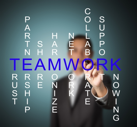 business man writing teamwork concept by crossword of relate word such as trust, partnership, share, collaborate etc. Stock Photo - 13417101