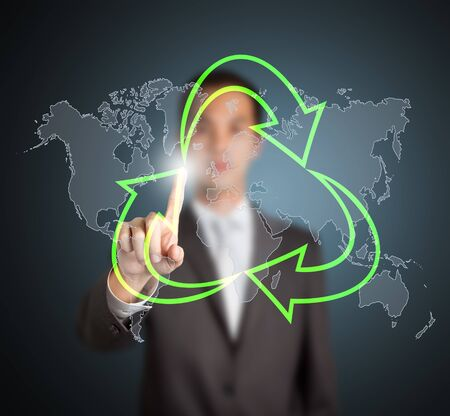 business man pointing at green recycle symbol with world map background photo