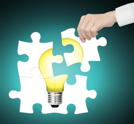 hand completing jigsaw puzzle of light bulb, sign of idea, innovation, creative, smart, vision, solution, energy, electric etc.