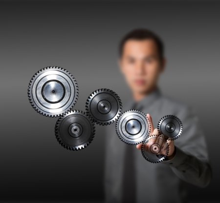 business man driving set of gears, concept of industry, machine, teamwork, power, and advance