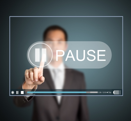 pause button: business man push pause button on touch screen to hold video clip