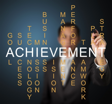 business man writing business concept by crossword of components which make the achievement such as success, performance, plan, strategy, management, teamwork, etc  Stock Photo