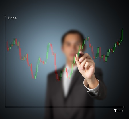 analyse: business man writing candle stick graph to analyze stock and made investment decision