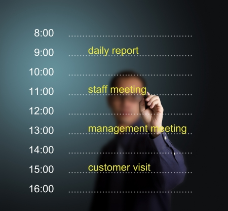 business man writing daily appointment schedule photo