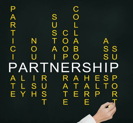 relate: business man hand writing partnership concept by crossword of relate word such as ally, sustain, help, support, assist, share, etc  Stock Photo