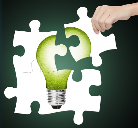 idea lamp: hand completing jigsaw puzzle of  green energy light bulb, sign of environment saving Stock Photo