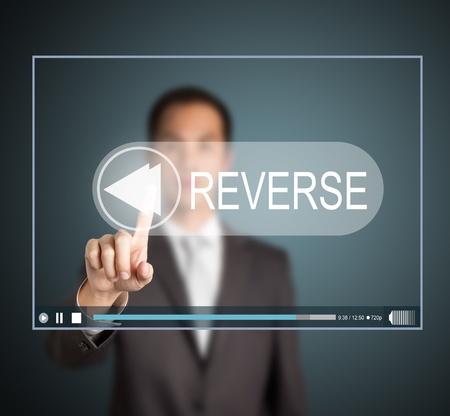 business man push reverse button on touch screen to invert video clip Stock Photo - 14123806