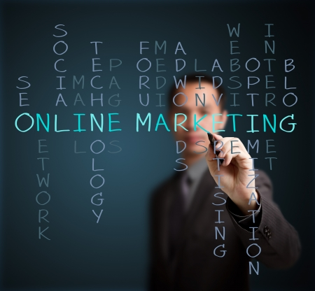 business man writing online marketing  concept by crossword of relate word such as internet, technology, advertising, seo, website, media, etc  Stock Photo
