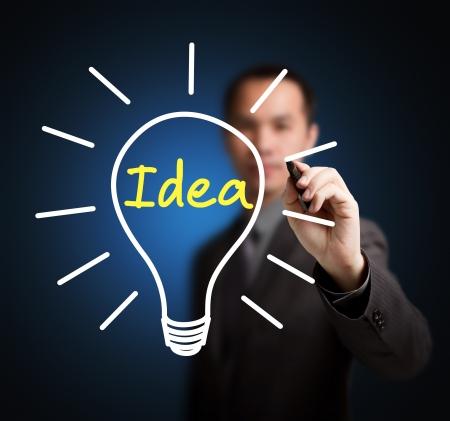 hombre escribiendo: hombre de negocios por escrito idea de bombilla
