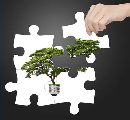 combining: hand completing jigsaw puzzle of alternative green energy light bulb, sign of environment saving