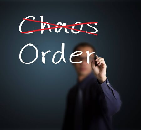 disorganize: business man eliminate chaos and make order Stock Photo