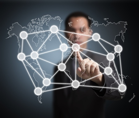 business man pointing at global network on world map photo