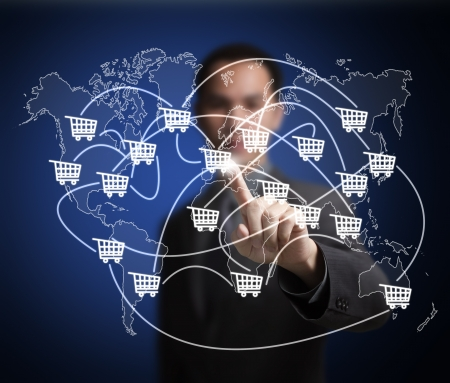 worldwide website: business man pointing at worldwide cart network on world map -  symbol of modern online trade and marketing
