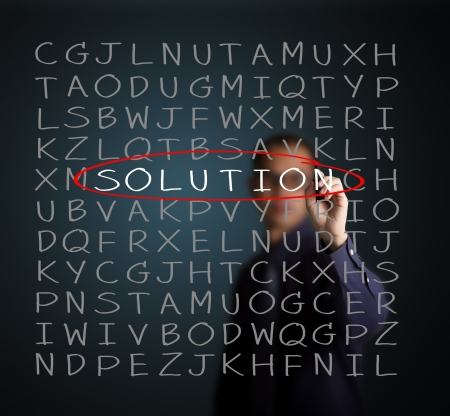 find solution: business man find solution on random alphabet puzzle Stock Photo