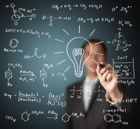 smart teacher writing various high school chemistry formula with light bulb   symbol of idea and solution   photo