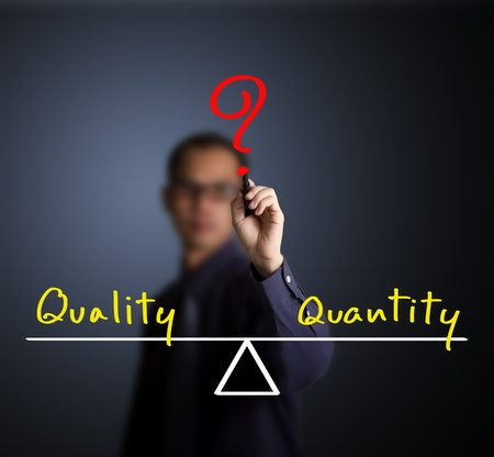 quality questions: business man writing quality and quantity compare on balance bar Stock Photo