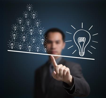unequal: Concepto de una gran idea es m�s importante que muchas peque�as ideas. Express by contrapeso en la punta del dedo del hombre de negocios.