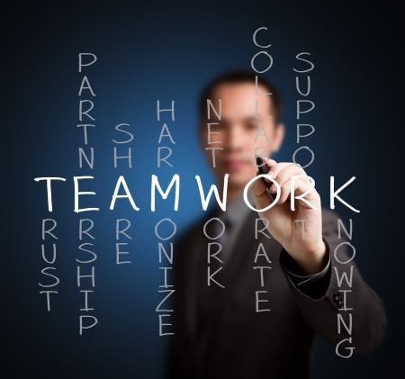 harmonize: business man writing teamwork concept by crossword of relate word such as trust, partnership, share, collaborate, support, etc