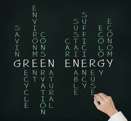business hand writing green energy concept by crossword on chalkboard photo