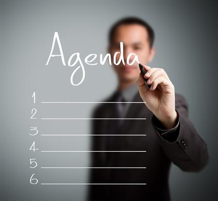 cronograma: hombre de negocios por escrito en blanco lista de la agenda