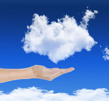 hand holding cloud in blue sky, symbol of cloud computing technology photo