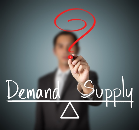 in demand: business man writing demand and supply compare on balance bar