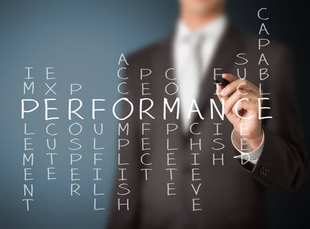 performance management: business man writing performance concept by crossword