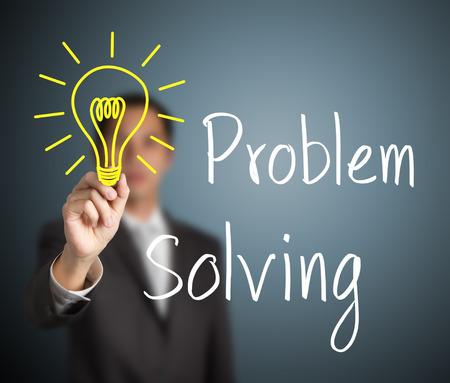 solving: business man writing problem solving light bulb Stock Photo