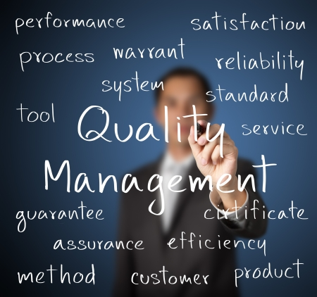 品質管理の概念を書くビジネス男 写真素材