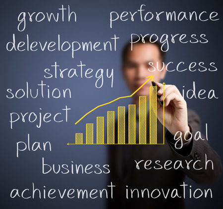 business man writing growth graph with business related text Stock Photo - 24961528