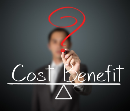 business man writing cost and benefit compare on balance bar