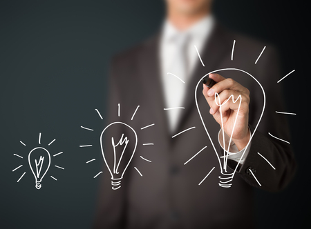 energy efficiency: business man writing growing idea lightbulb