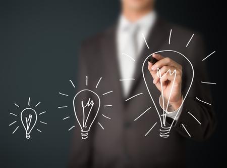 eficiencia energetica: hombre de negocios por escrito creciente idea bombilla