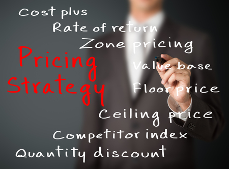 business man writing pricing strategy of marketing concept