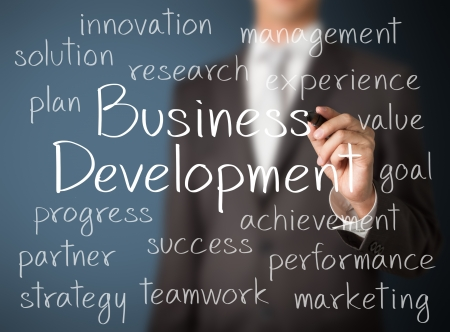 business development: business man writing business development concept