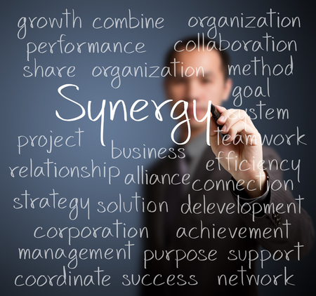 synergy: business man writing synergy concept Stock Photo