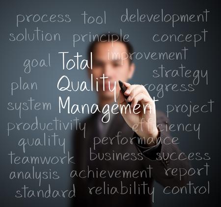 business man writing total quality management  TQM  concept photo