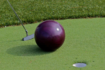 Golfer trying to putt a bowling ball into the cup  photo