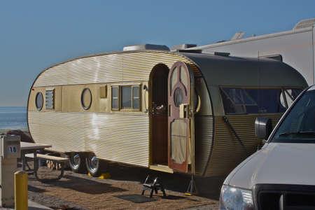 Vintage gold travel trailer camping at beach Standard-Bild