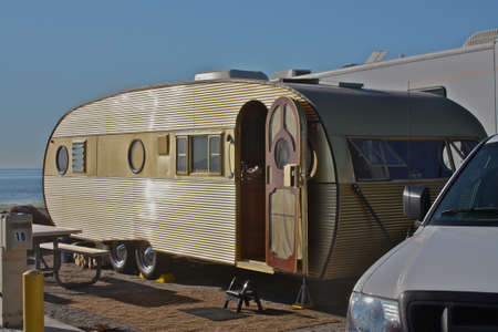 Vintage gold travel trailer camping at beach Foto de archivo