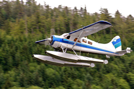 fixed wing aircraft: Seaplane, loaded with cargo, flies overhead with forested background Stock Photo