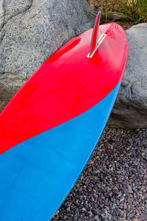 concave: Red and blue surfboard lying against large rocks
