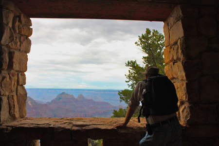Hiker Viewing The North Rim Of The Grand Canyon Through Open Air